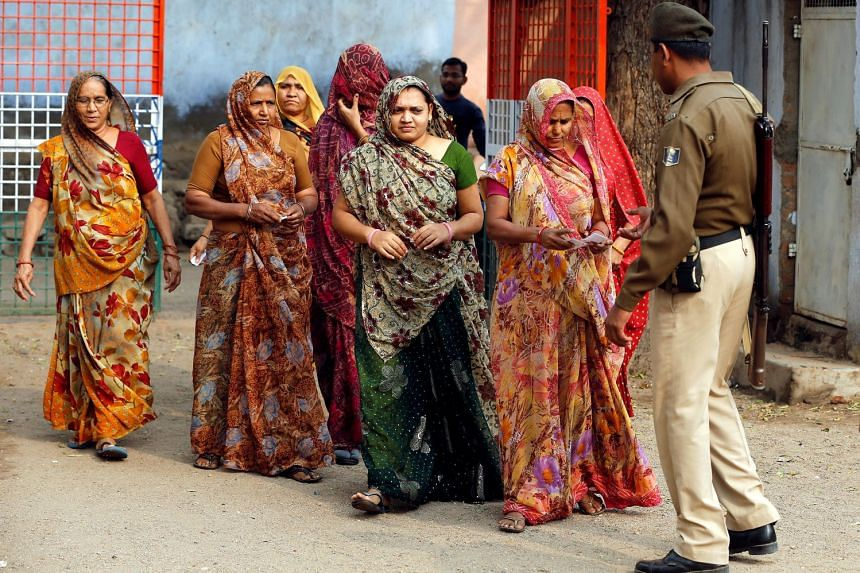 A policeman checks identity papers of women arriving to cast their votes at a polling station in the Panshina village of Surendranagar district on Dec 9, 2017.