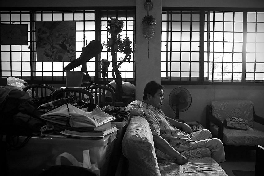 Mr Tay Cheng Tian in his four-room flat in Choa Chu Kang during a visit home in October. On the windows hang artwork done by his niece.
