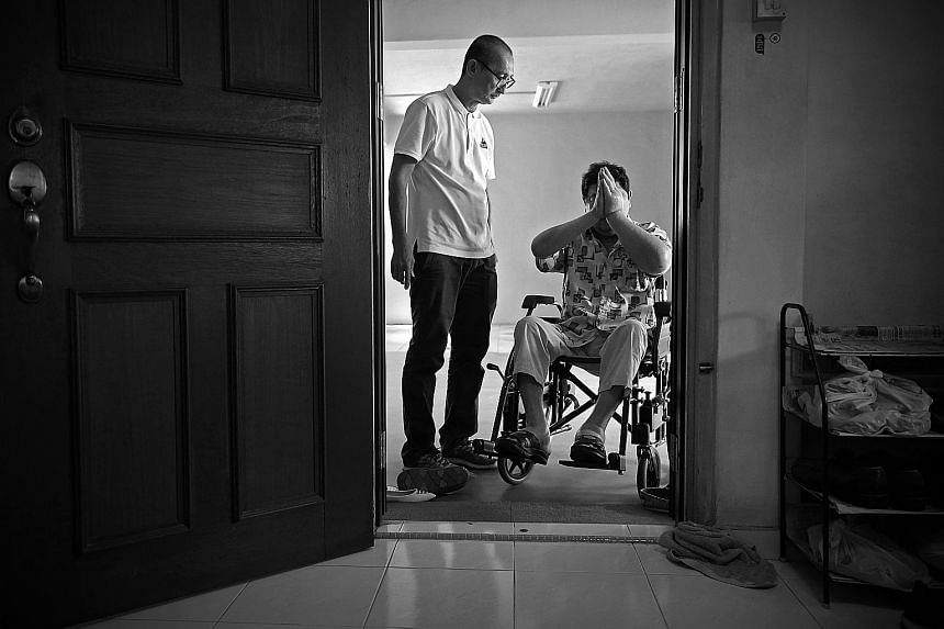 Volunteer Paul Koh looking on as Mr Tay paid his respects to the gods before leaving his sister's flat, during a home visit in October. Volunteer Jaki Fisher, 39, who runs the No One Dies Alone (Noda) project, keeping an eye on Mr Tay during a late-n