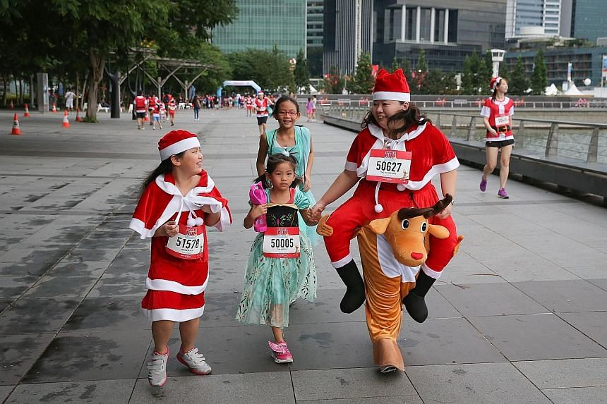 Participants gamely donned Christmas costumes for the annual Santa Run For Wishes along Marina Bay yesterday. The annual fund-raising event was into its fourth year, and saw 3,300 participants. They were encouraged to dress as their favourite Christm