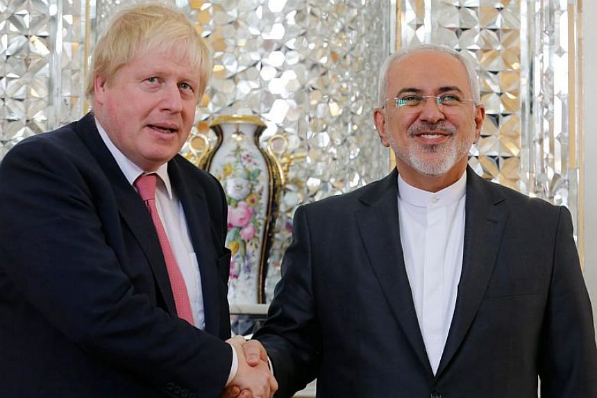 Iran's Foreign Minister Mohammad Javad Zarif (right) shakes hands with his British counterpart Boris Johnson during a meeting in Tehran on Dec 9, 2017.