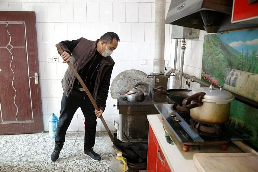 A man shovels coal into a tray next to an oven he uses to heat his home in his kitchen in the village of Heqiaoxiang outside of Hebei province, China on Dec 5, 2017.