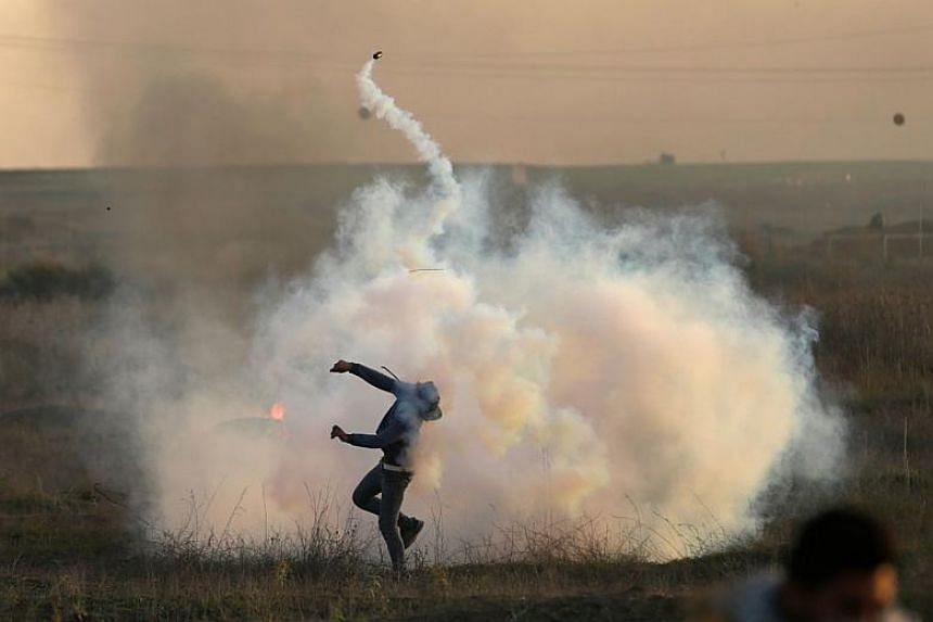 A Palestinian protester throws a tear gas canister back at Israeli forces during clashes near the Israel-Gaza border east of Gaza City.