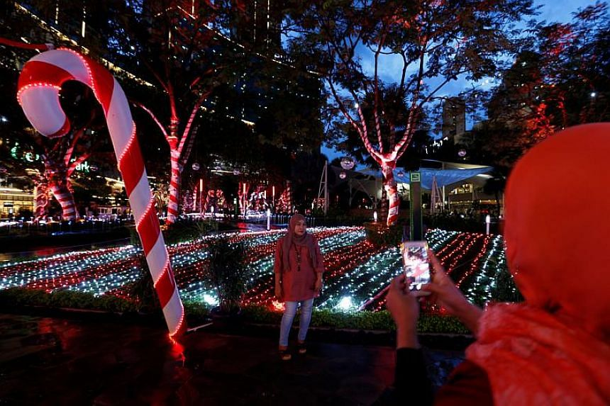 Women taking pictures near Christmas decorations to celebrate the upcoming festive season at Tribeca Park in Jakarta, Indonesia.