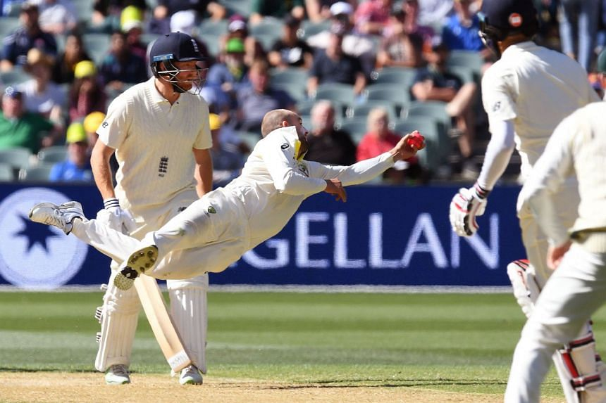 Australian spinner Nathan Lyon dives to take a catch to dismiss England batsman Moeen Ali (second from right) as fellow batsman Jonny Bairstow (left) looks on on the third day of the second Ashes cricket Test match in Adelaide in Dec 4, 2017.
