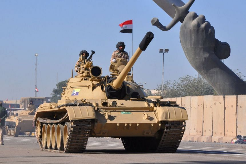 A column of Iraqi army tanks parading in Baghdad's fortified Green Zone, during a victory parade on Dec 10, 2017.