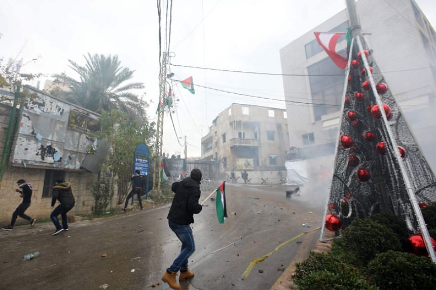 Lebanese security forces fire tear gas to disperse protestors during a demonstration outside the US embassy in Awkar, on the outskirts of Beirut, on Dec 10, 2017.