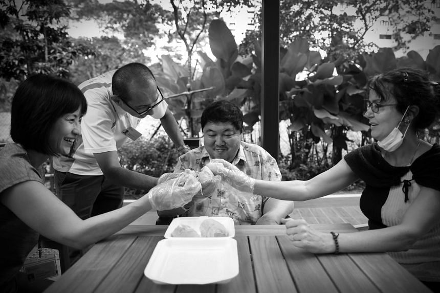 Always game to try something new, Mr Tay indulges in his first taste of Mao Shan Wang durians in the hospice garden with volunteers Tio Guat Kuan, Paul Koh and Jaki Fisher. The food lover had never tried the expensive premium durian before and wanted