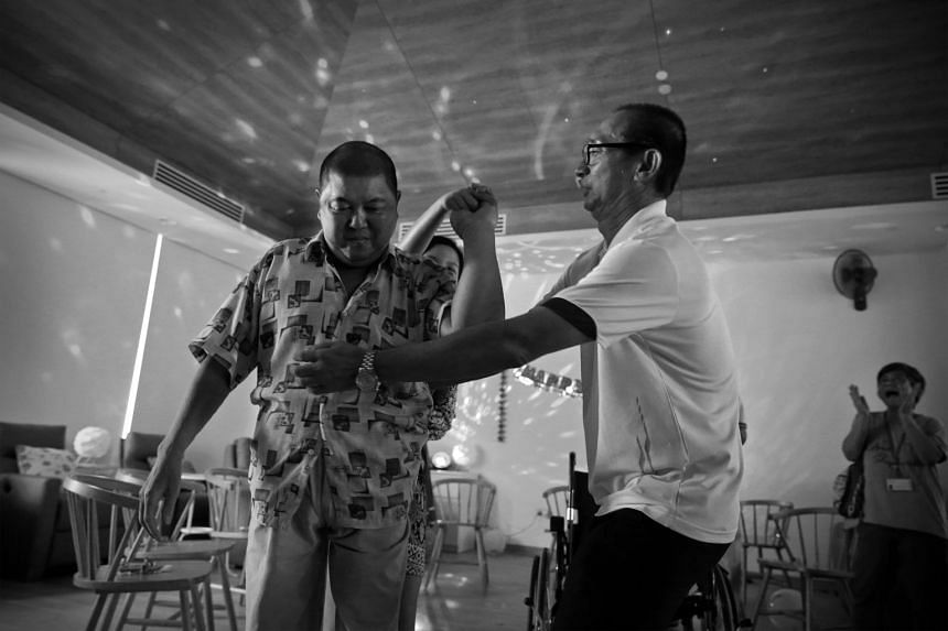 Mr Tay doing a waltz with volunteer Toh Qi (behind) during his birthday party at the hospice with the help of volunteer Paul Koh. Despite swollen feet, Mr Tay manages to dance to a hit song by Cantopop queen Sally Yeh for five minutes. He later becom