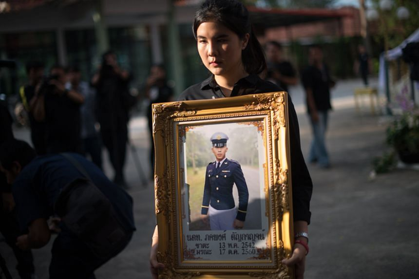 Supicha Tanyakan, the sister of Pakapong Tanyakan, a first year cadet in the Thai army, carries his photo during a cremation ceremony in Chonburi on Dec 10, 2017.