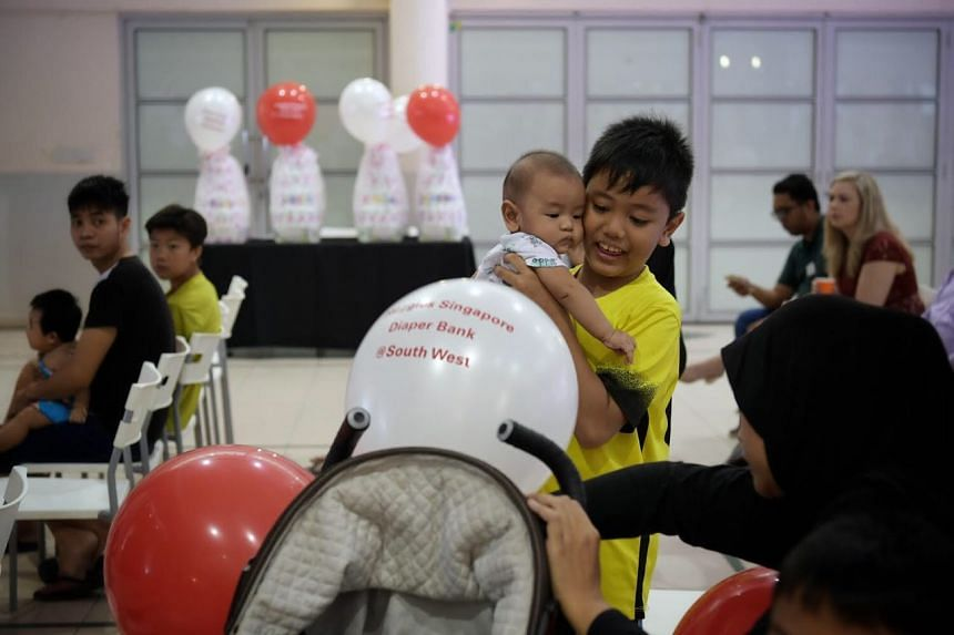 Mohamad Rayyan Hambali, 9, with his baby brother, three-month-old Mohamad Rayyan Naqeeb, at the launch of Singapore's first diaper bank held at the Jurong Spring Community Club.