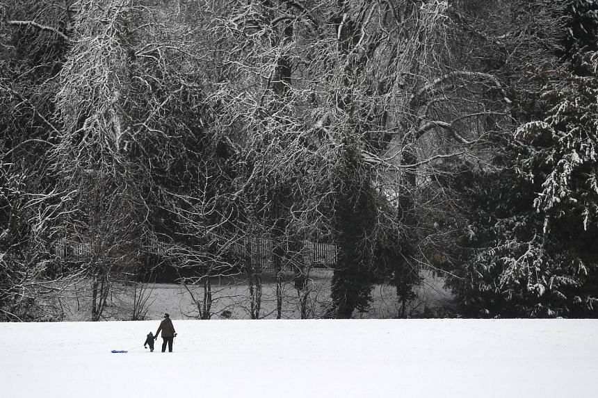 People walking on the snow in a park in High Wycombe, 48km north-west of London, yesterday. Amber weather warnings have been issued after heavy snow affected large areas of Britain. Cars moving on the snow-covered highway A25 in Godewaersvelde, north