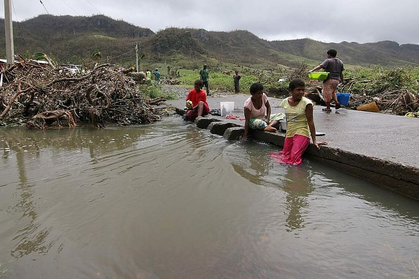 Fiji residents of a settlement damaged by Cyclone Winston last year are shown in this New Zealand Defence Force photo. Worsening extreme weather events have forced entire communities on low-lying Pacific Islands to relocate. There are growing calls f