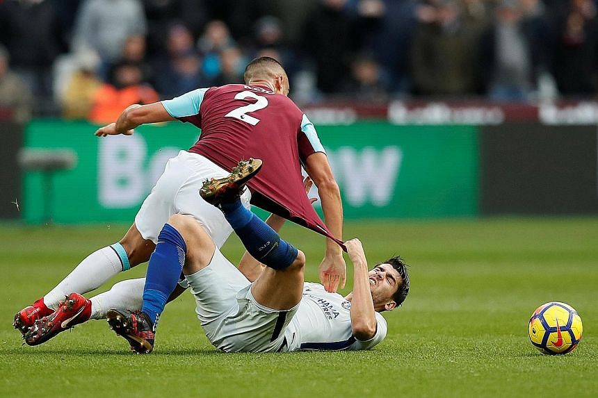 Chelsea striker Alvaro Morata gets to grips with West Ham defender Winston Reid on Saturday. The defending champions have already lost four times this season, once fewer than the whole of last season.