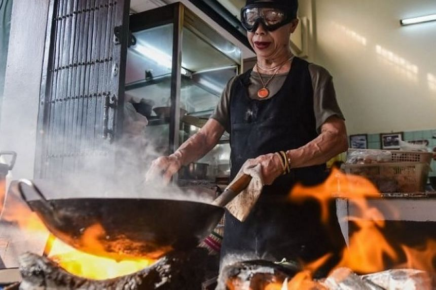Supinya Junsuta, better known as Jay Fai, wears oversized goggles while cooking her signature dish of crabmeat omelette over charcoal, Her eatery is the only street food venue in Bangkok to have earned one Michelin star.