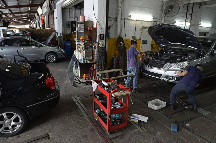 File photo of automotive workers working on a car at a workshop at Sin Ming Drive.