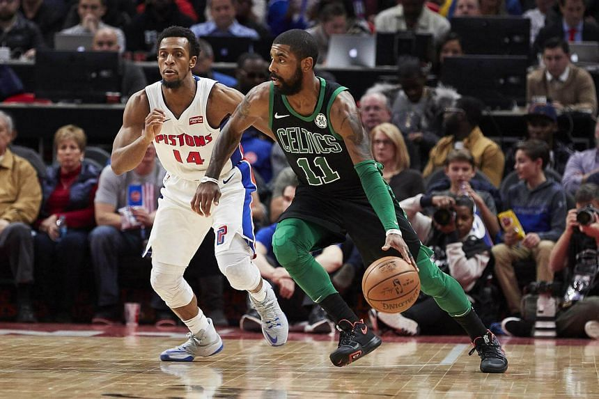 Boston Celtics guard Kyrie Irving dribbles the ball beside Detroit Pistons guard Ish Smith in the second half of the game.