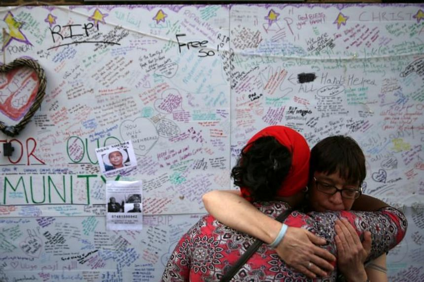 Two women embracing in front of messages left on a wall of condolence following the blaze that killed 70 people at Grenfell Tower.