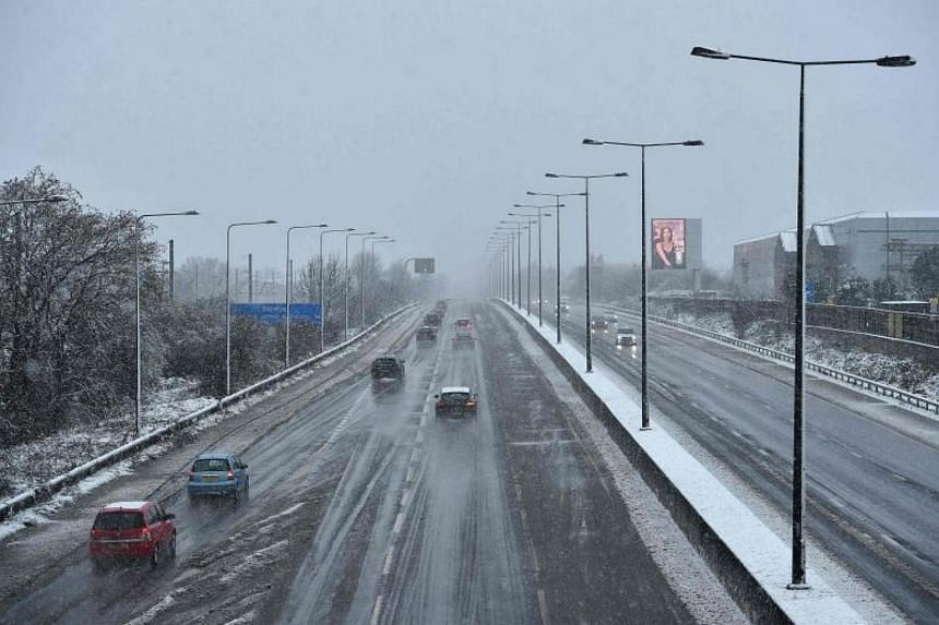 Motorists travel on a snowy day along the M1 Highway on the outskirts of London on Dec 10, 2017.