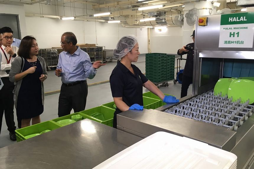 Minister for the Environment and Water Resources Masagos Zulkifli being given a tour of Changi Terminal 3's central dishwashing area on Dec 11, 2017.