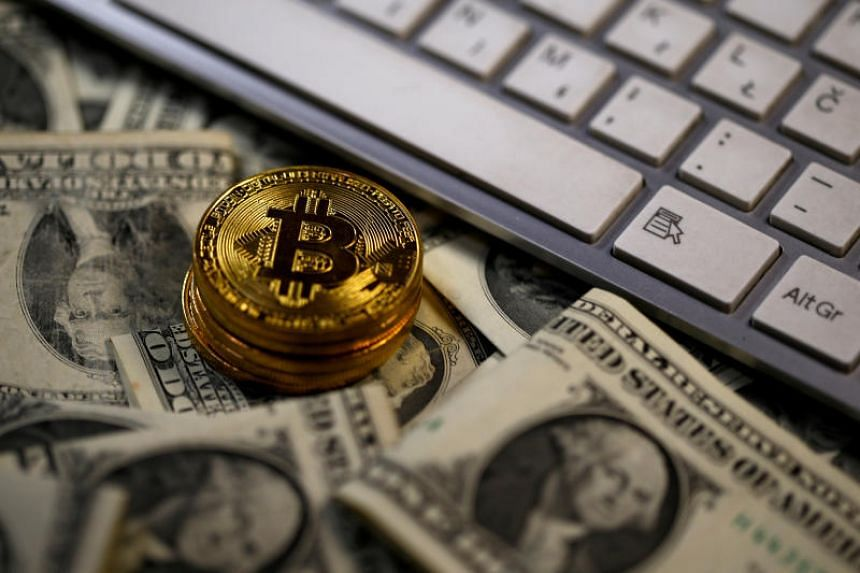 Bitcoin (virtual currency) coins placed on dollar banknotes.