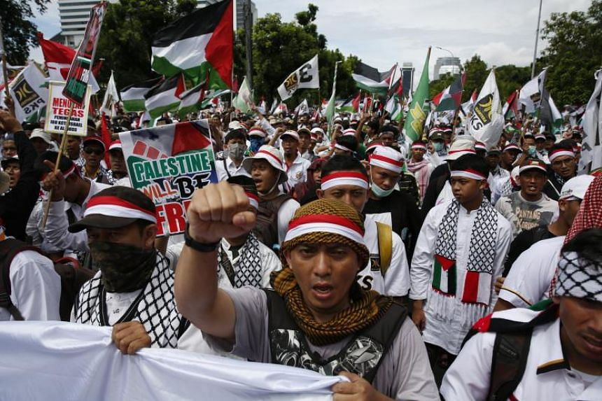 Indonesian Muslim activists hold pro-Palestinian placards during a protest against US President Donald Trump's decision to recognise Jerusalem as capital of Israel, outside of the US embassy in Jakarta, Indonesia, on Dec 10, 2017.