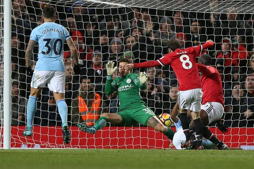 Manchester City's Ederson makes a double save from Manchester United's Zlatan Ibrahimovic (right) and Juan Mata (2nd right) during the English premier league soccer match at Old Trafford Stadium in Manchester, Britain, on Dec 10, 2017.
