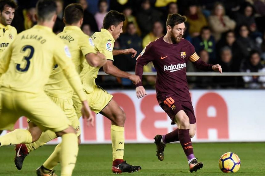 Villarreal's midfielder Rodrigo Hernandez (left) vies with Barcelona's Argentinian forward Lionel Messi during the Spanish league football match between Villarreal CF and FC Barcelona at La Ceramica stadium in Vila-real on Dec 10, 2017.