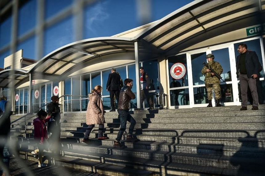 People enter the courthouse as Turkish special force soldiers stand guard at the entrance, on Dec 11, 2017 at Silivri district in Istanbul, on the opening day of the trial of an Uzbek citizen who confessed to killing 39 people at an Istanbul nightclu