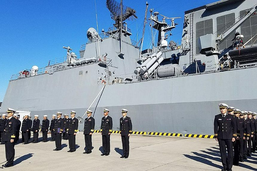 Soldiers at a welcome ceremony for South Korea's destroyer the Ganggamchan and logistic supporting vessel the Hwacheon in the Japanese port city of Yokosuka in Kanagawa prefecture yesterday, as the US, Japan and South Korea kicked off a two-day joint