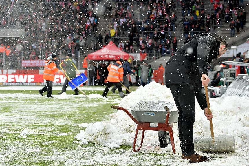 GERMANY: Ground staff removing snow (right) from the pitch prior to the German Bundesliga football match between FC Cologne and SC Freiburg in Cologne on Saturday. BRITAIN: A sign (left) alerting drivers to road closures near Wrexham, north Wales, ye