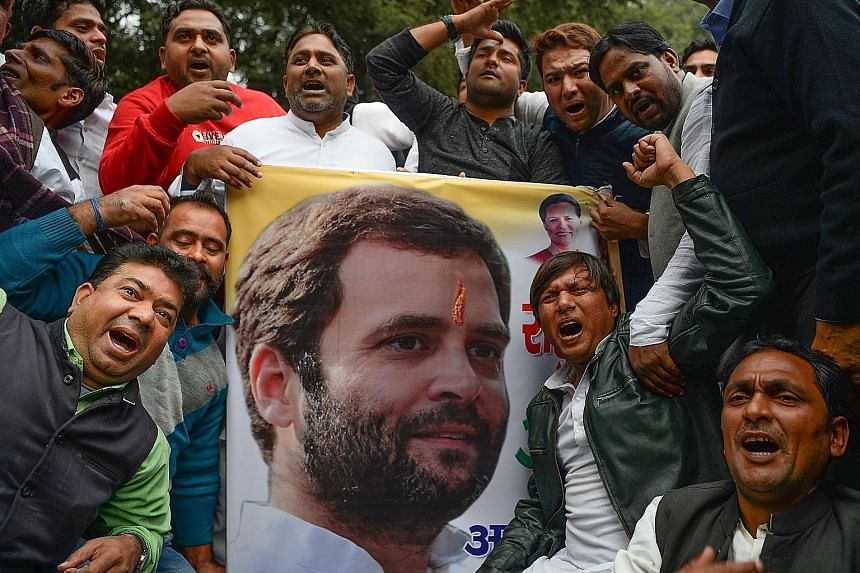 Jubilant supporters of India's opposition Congress Party with a poster of Mr Rahul Gandhi after he was named president yesterday, taking over the 132-year-old party from his mother Sonia Gandhi.
