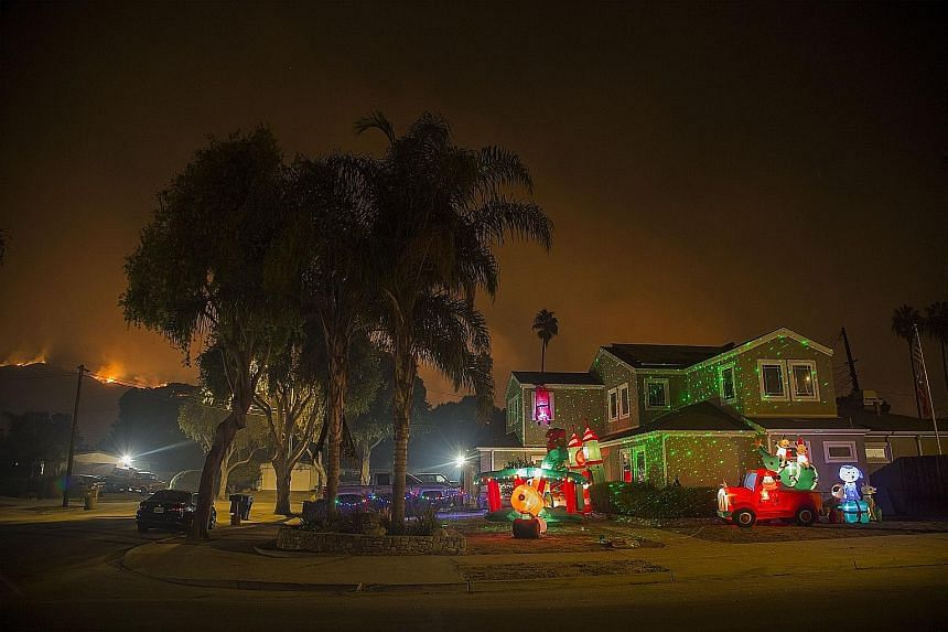 Left: Christmas decorations illuminating a house as the growing Thomas Fire advances towards the Santa Barbara County seaside communities on Sunday. Above: People watching the Thomas Fire from a distance in Carpinteria, California.