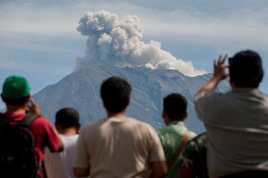 People watch as Mount Agung spews ash and smoke during an eruption from an obeservation post in Bali.