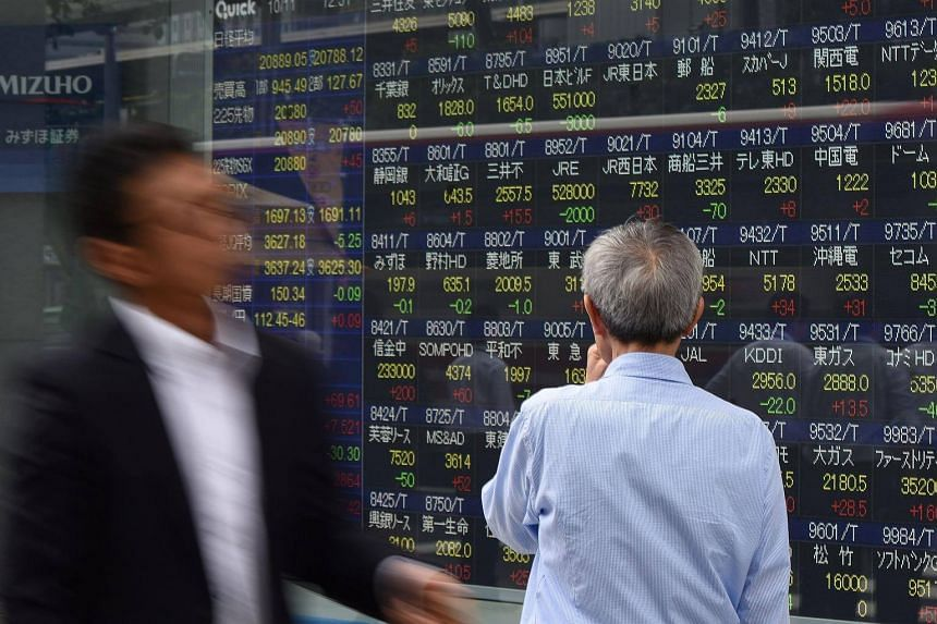 A pedestrian looks at an electronic stocks indicator displaying numbers of the Tokyo Stock Exchange in Japan.