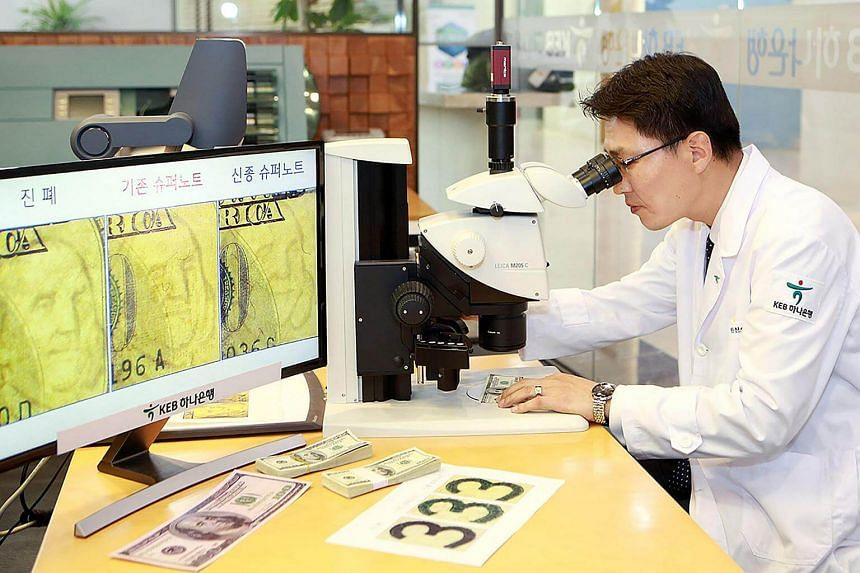 Head of the KEB Hana Bank's anti-counterfeit centre Yi Ho Joong inspects a fake US$100 banknote at the bank in Seoul.