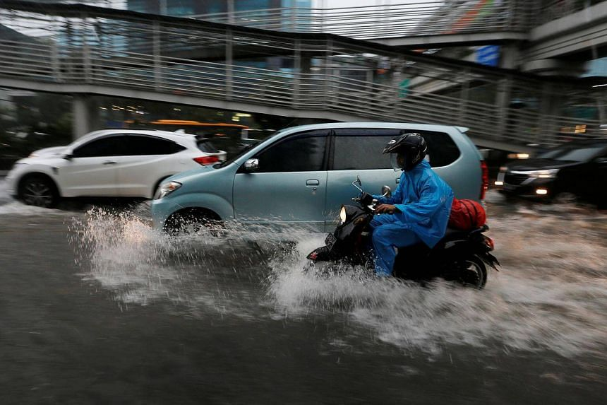 Traffic on a flooded street at a business district in Jakarta.