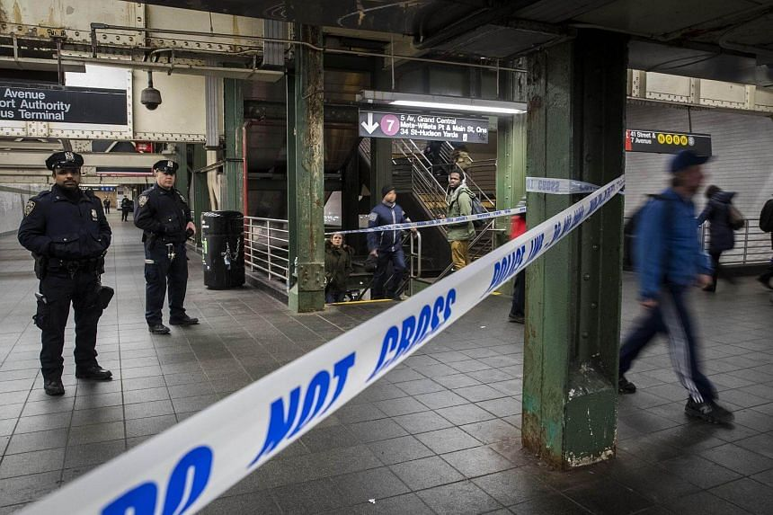 Commuters exit a train as police officers stand in a closed-off underground walkway near the site of a pipe bomb explosion in New York.