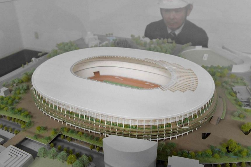 An official of the Japan Sports Council looking at a model of the new National Stadium which is under construction in Tokyo.