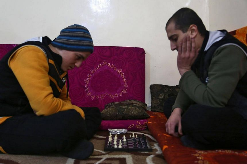 Mohammed Haj Ahmad (right) plays chess with his roommate at the Syrian Centre for Countering Extremist Ideology in the Syrian town of Marea, in the northern Aleppo district.