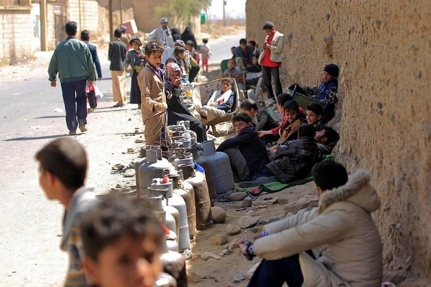 Yemenis wait next to empty gas cylinders for gas supplies amid increasing shortages in the Yemeni capital Sanaa.