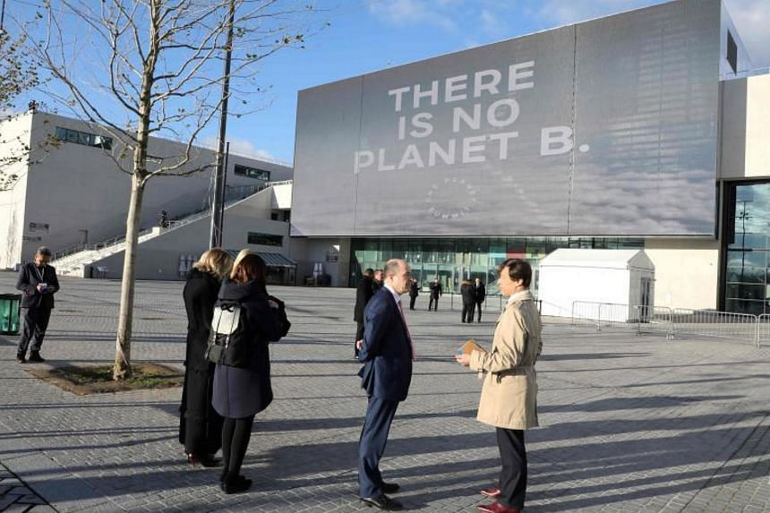 People stand outside the La Seine Musicale venue on l'ile Seguin in Boulogne-Billancourt, west of Paris, on Dec 12, 2017 during the One Planet Summit.