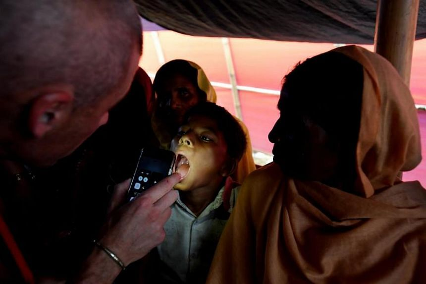 A nurse checks the throat of a boy with a fever for diphtheria at the Balukhali refugee camp in Bangladesh on Dec 11, 2017.