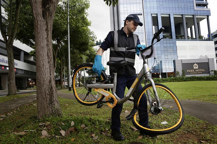 "Mr Zhivko Girginov picking up a damaged oBike on one of his ""raids"", where he collects such damaged share bikes and deposits them in a public space so operators can pick them up."