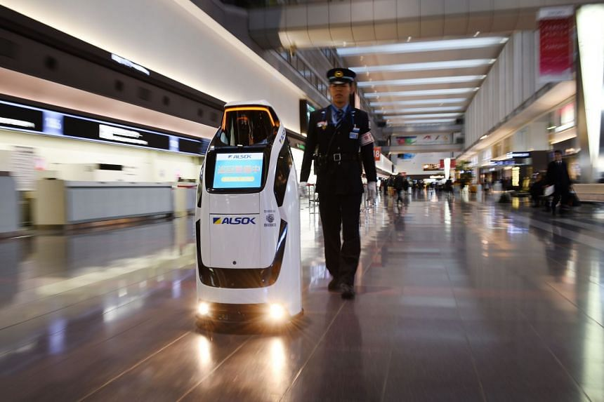 Security and guide robot Reborg-X, from security firm Alsok, patrolling Haneda airport with a security officer, during a demonstration on Dec 12, 2017.