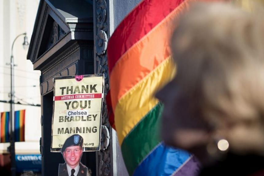 People holding up signs during a celebration for transgender soldier Chelsea Manning in the Castro District of San Francisco, California during a celebration for Manning's release on May 17, 2017.