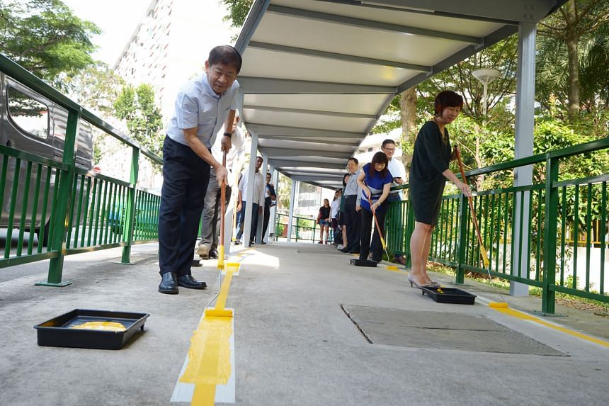 There are rest stops with seats along the sheltered walkway between Redhill MRT station and the Enabling Village. Transport Minister Khaw Boon Wan painting the final stretch of the yellow lines along the walkway, with SG Enable chief executive Ku Geo