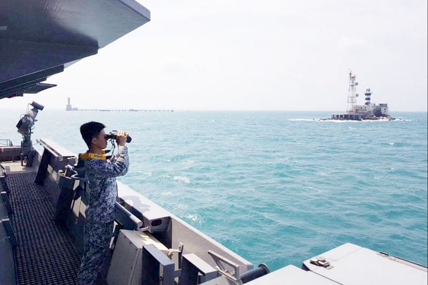 A crew member of RSS Sovereignty scanning the horizon for the missing men. He is looking at Pedra Branca, and Middle Rocks is to his left.
