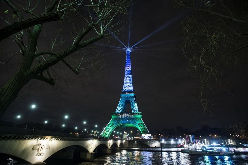 The Eiffel Tower illuminated in green and blue, the colours of the One Planet Summit, in Paris, France.
