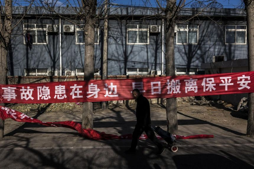 A migrant worker vacating his home walks past a banner declaring a building to be a fire hazard in Beijing on Dec 4.